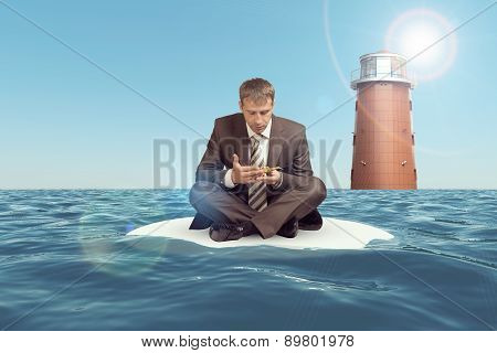 Businessman sitting in lotus position on sand