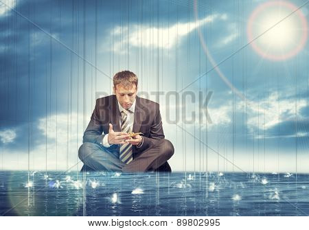 Businessman sitting in lotus position on water