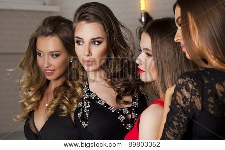 Close up portrait of four beautiful glamorous young women in studio