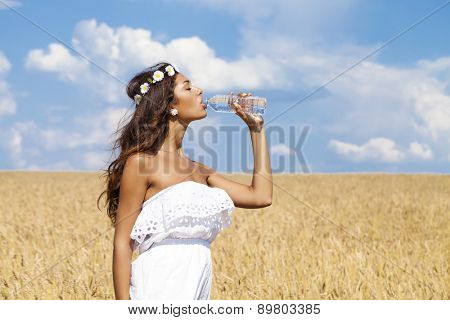 Young beautiful woman quenches thirst in a wheat golden field