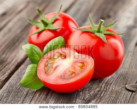 Tomato with basil on a wooden background