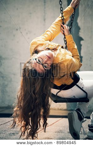 young urban woman with eyeglasses have fun on swing in the city