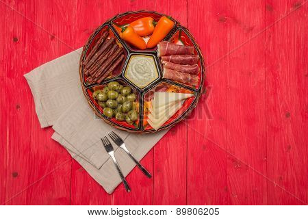 Basket With Several Spanish Tapas On Red Table