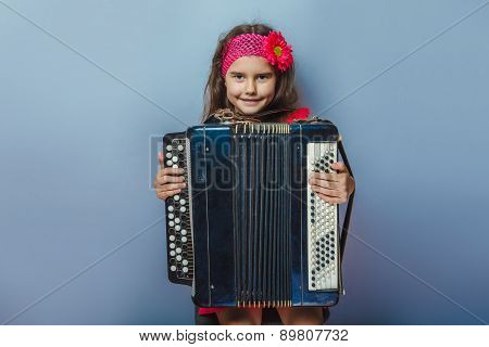 teen girl of European appearance five years holds the accordion
