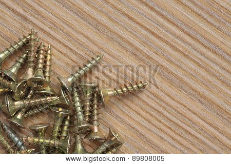 Screws On A Wooden Background Close Up.