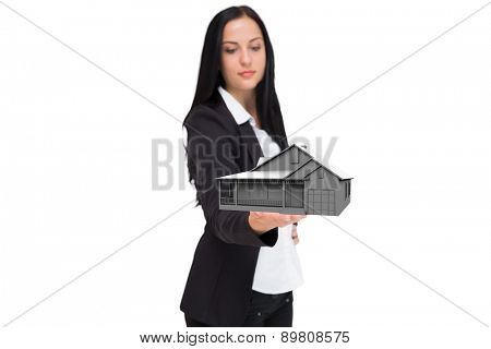 Pretty businesswoman presenting with hand against graphic house