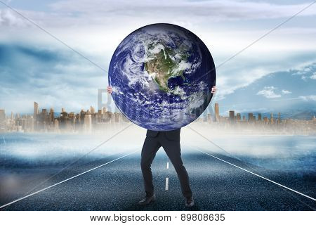 Businessman carrying the world against large city on the horizon