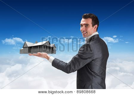 Businessman presenting with hand against bright blue sky over clouds