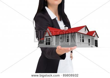 Pretty businesswoman presenting with hand against 3d house