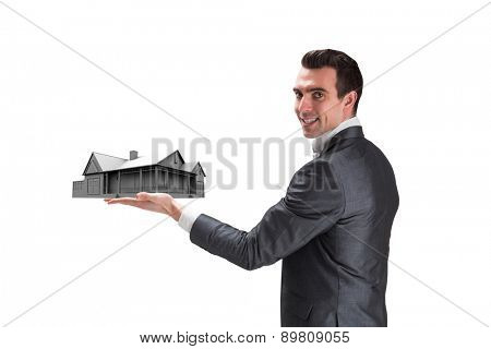 Businessman presenting with hand against graphic house