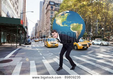 Businessman carrying the world against new york street