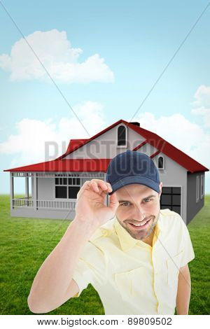Handsome delivery man wearing baseball cap against blue sky