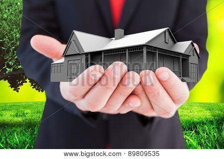 Businessman presenting with his hands against field against glowing lights