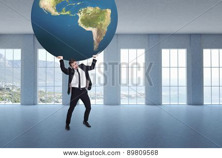 Businessman carrying the world against room overlooking ocean