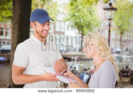 Happy delivery man getting signature from customer against canal in amsterdam