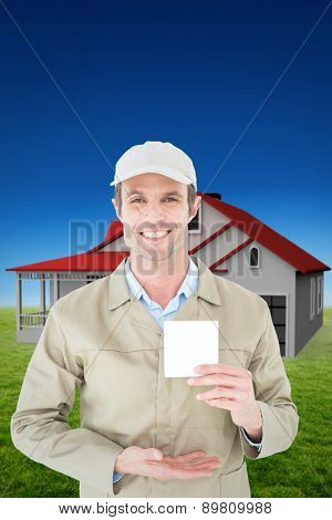 Happy delivery man showing blank note against blue sky