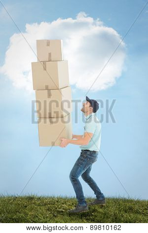 Shocked delivery man carrying stack of boxes against blue sky over green field