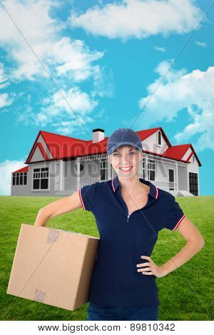 Happy delivery woman holding cardboard box against blue sky