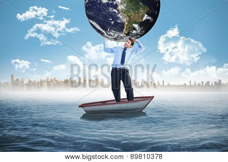 Businessman carrying the world against small boat in the sea with city on horizon