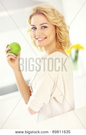 A picture of a young woman eating apple in the kitchen