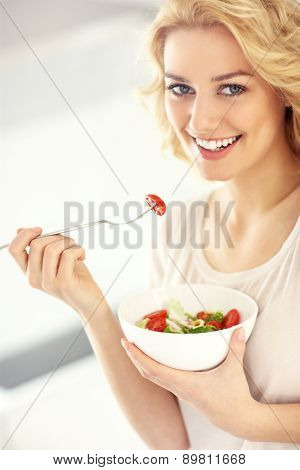 A picture of a young woman eating salad in the kitchen