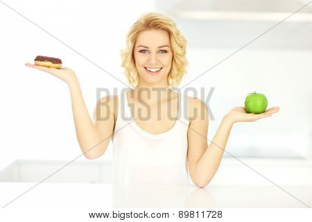 A picture of a happy woman with donut and apple in the kitchen