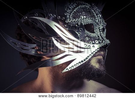 Shiny, bearded man with silver mask Venetian style. Mystery and renaissance