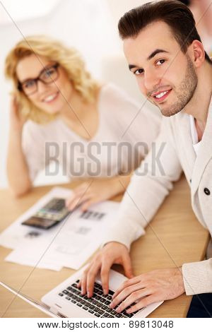 A picture of a young couple working on documents at home