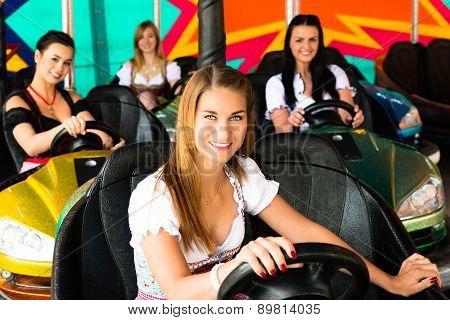 Beautiful girls in an electric bumper car in amusement park