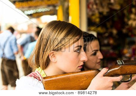 Two attractive girls playing shooting games at German funfair