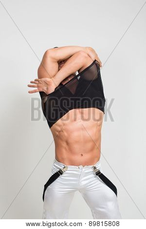 Muscular sexy man taking off t shirt. Sexy stripper undressing.