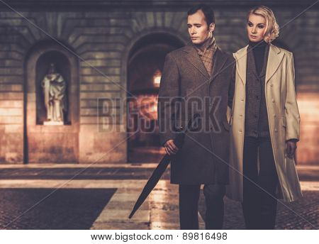 Elegant couple in coats against building facade in evening