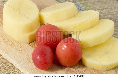 Tomatoes And Potatoes On A Wooden Board