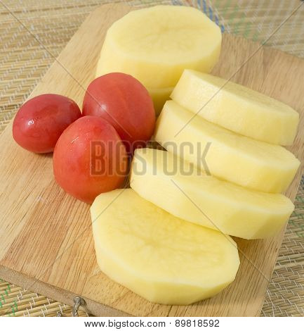 Fresh Tomatoes And Potatoes On Wooden Board