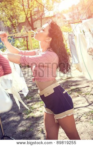 Pin up, vintage style photo of woman doing laundry and smoking.