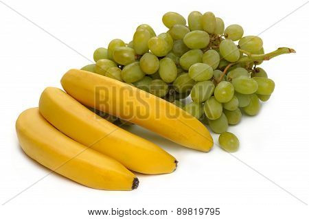 Three banana and a bunch of green grapes on a white background