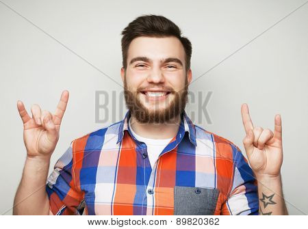 emotional and people concept: young bearded man showing heavy gesture over grey background