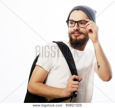 people, travel, tourism and education concept - happy young bearded man in eyeglasses wearing hat, with backpack over white  background