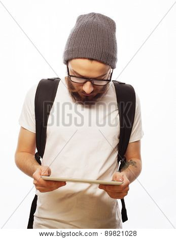 people, travel, tourism and technology concept - happy young bearded man in eyeglasses with backpack and  tablet  over white  background. Hipster style. Positive emotions.