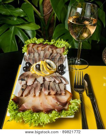 Herring decorated with lemon, onion and parsley on a yellow, black background