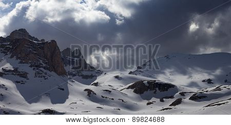 Panoramic View On Snowy Mountains In Storm Clouds