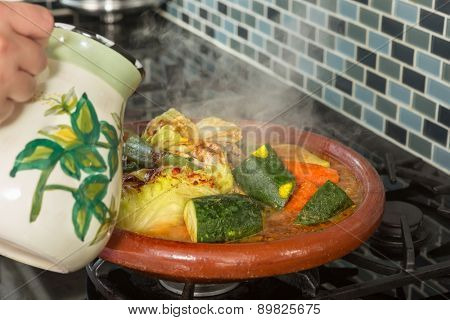 Hands of a woman adding water to a traditional Moroccan tajine during Ramadan nights (Moroccan immigrant woman in modern European kitchen)