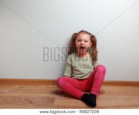 Happy Crying Kid With Open Mouth Sitting On The Floor