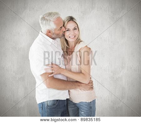Affectionate man kissing his wife on the cheek against weathered surface