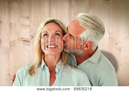 Affectionate man kissing his wife on the cheek against wooden planks
