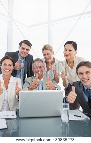 Group of happy business colleagues with laptop gesturing thumbs up at office desk