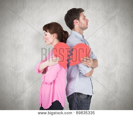Couple holding a broken heart against weathered surface