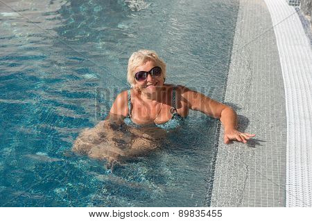 Aged Woman In Splashes On Blue Water Of Pool Background.