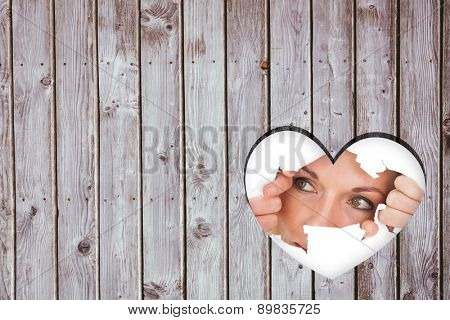 Woman looking through torn paper against heart in wood