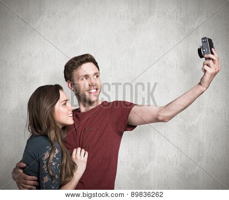 Couple taking selfie with digital camera against weathered surface